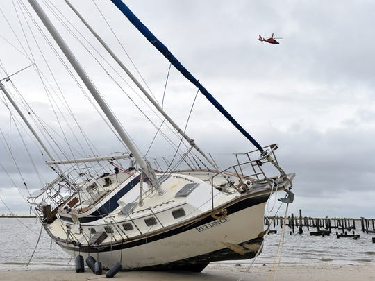 A U.S. Coast Guard helicopter flies over a beached sail boat near Margaritaville and the Golden Nugget in Biloxi Sunday, October 8, 2017, after Hurricane Nate made landfall on the Gulf Coast.