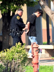 Police walk with 16-year-old Nathaniel Jouett, who