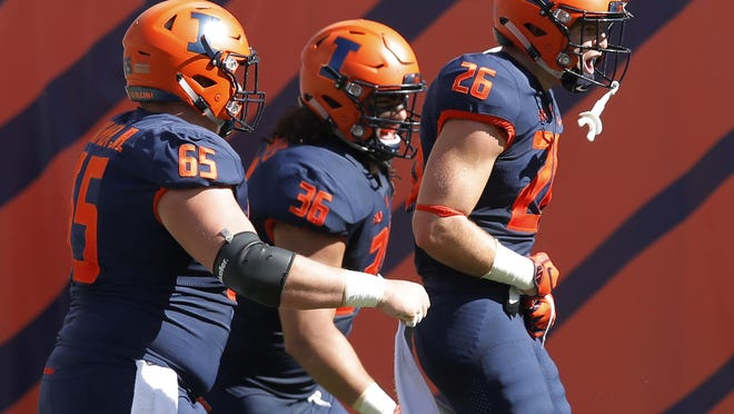Illinois's Mike Epstein, right, celebrates his touchdown against South Florida with teammates Doug Kramer, left, and Austin Roberts during the first half of an NCAA college football game Saturday, Sept. 15, 2018, in Chicago.