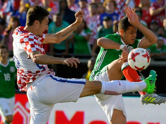 FILE - In this Saturday, May 27, 2017 file photo, Croatia defender Zoran Nizic, left, and Mexico forward Javier Hernandez go after the ball during the second half of a soccer match, in Los Angeles. (AP Photo/Mark J. Terrill, File)