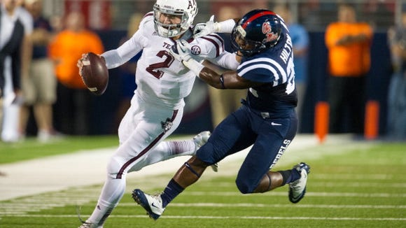 OXFORD, MS - OCTOBER 12:  Quarterback Johnny Manziel #2 of the Texas A&M Aggies attempts to maneuver by defensive back Mike Hilton #28 of the Ole Miss Rebels on October 12, 2013 at Vaught-Hemingway Stadium in Oxford, Mississippi. At halftime Texas A&M leads Ole Miss 14-10.  (Photo by Michael Chang/Getty Images)