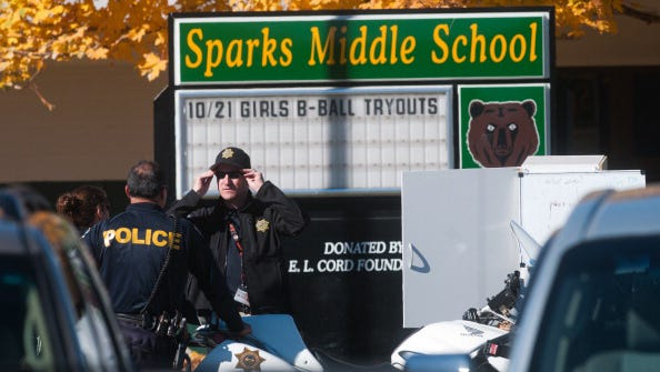 Law enforcement gather in the parking lot after a shooting at Sparks Middle School Oct. 21, 2013. A staff member was killed and two students were injured after a student opened fire at the Nevada middle school. The suspected gunman was also killed.