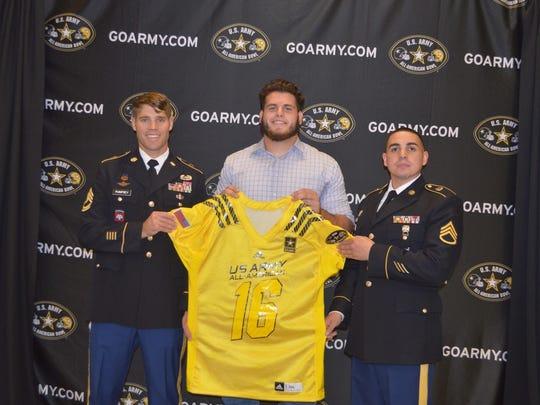 Army representatives Sergeant First Class Max Pumfrey and Staff Sergeant Carlos Rodriguez present Garrett Rand his jersey.