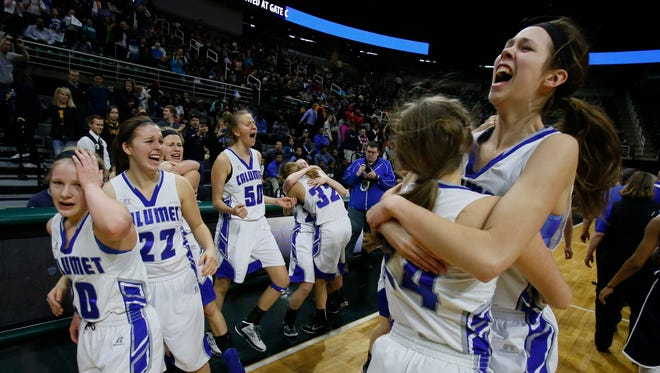 Calumet's Hailey Wickstrom, top right, spins around in the arms of teammate Anne Sturos as they celebrate their 57-49 win over Flint Hamady in the MHSAA Class C girls basketball final on Saturday, March 21, 2015 in East Lansing.