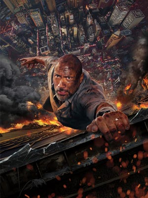 "This image released by Universal Pictures shows Dwayne Johnson in a scene from ""Skyscraper."" (Universal Pictures via AP)"