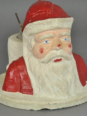 This rather serious Santa is a Christmas tree stand made of concrete. It sold last year for $118, less than expected. The heavy stand was made for a feather tree not a natural tree that needed water.
