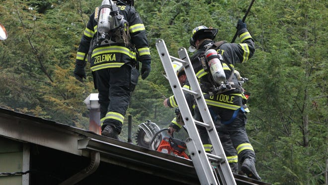 Firefighters control a house fire on Wilshire Drive in Spring Valley Aug. 22. The fire caused extensive damage to the house. The Spring Valley volunteer fire department uses older equipment, worn-down fire protection gear and boots, and depend on other departments for equipment hand-me-downs.