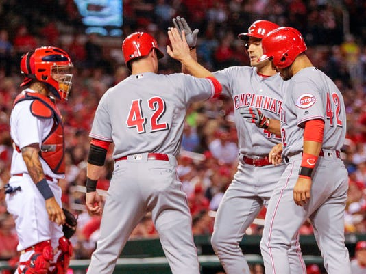 CORRECTS TO THIRD INNING NOT FOURTH INNING - Cincinnati Reds' Joey Votto, second from right, celebrates with teammates Zack Cozart and Eugenio Suarez as St. Louis Cardinals' Yadier Molina, left, looks on in the third inning of a baseball game, Friday, April 15, 2016 in St. Louis. (AP Photo/Tom Gannam)