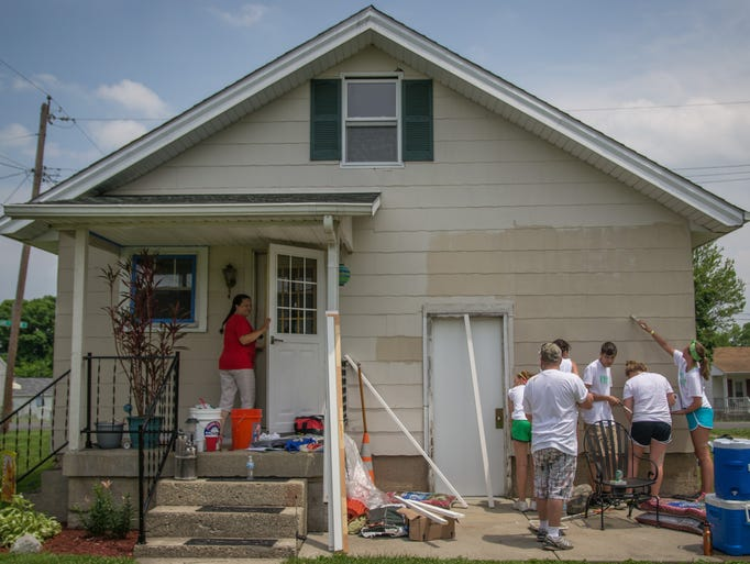 "DeAnna Couch, left, watches as student volunteers paint her house in Hamilton, Ohio Monday afternoon. High school youth groups from across the country participated in Group Workcamps in Cincinnati with Serves to Encourage Low-income Families (SELF) for a home repair blitz week in Hamilton to help families in physical and financial need. ""I just take it as a blessing, said Terry Couch, ""there's no way I'd have done it on my own."