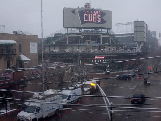 Snow falls at Wrigley Field on the morning of Chicago's home opener baseball game against the Pittsburgh Pirates, Monday, April 9, 2018, in Chicago. (AP Photo/Kiichiro Sato)