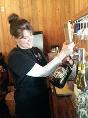 Marion Forks Restaurant co-owner Alicia Boyd fills a growler with suds from Santiam Brewery.