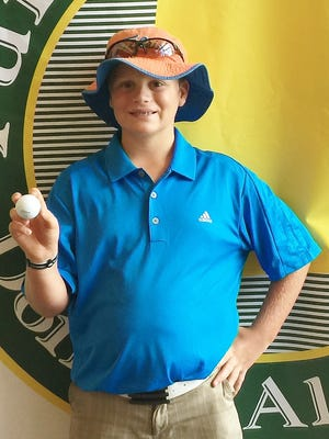 Tyler Williamson holds up his first hole-in-one after his round Monday.