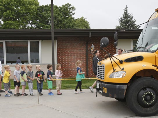 Children board a bus while learning about bus safety in 2013.