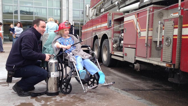 Burlington firefighter Kyle S. Trudo helps Jacob Hutchins of Burlington hose down a BFD fire truck during a burn awareness visit on Wednesday to the UVM Children's Hospital.
