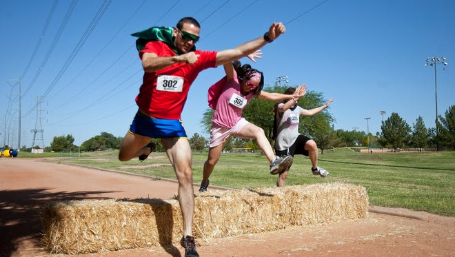 Joe Rockwood (left), Aubrey Rockwood (middle) and Veronica Chugg of Mesa leap bales of hay in a single bound at the KA-POW! Superhero Adventure Run at Freestone Park in Gilbert..