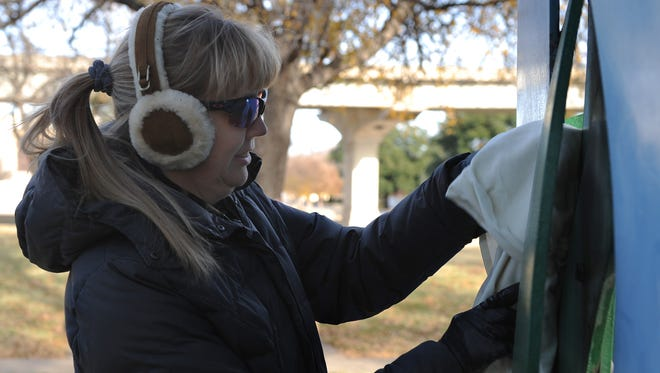Lori Jameson hangs clothes to the crape myrtle art piece for Scarves in the Park Sunday, Dec. 18, 2016, in Harold Jones Park on Holliday St. Scarves in the Park was brought to Wichita Falls by Jenny Hines who learned of a similar event in Virginia. Scarves, hats, coats, pants and hygiene products are collected and left in the park for people is take to keep warm and take care of themselves.