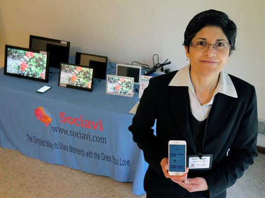 Paula Muller, founder of Sociavi, an internet-based product that helps seniors stay in touch with their families, while being much simpler to use than social media apps like Facebook, displays a variety of frame-like screens and the mobile app at her home office in Keyport.