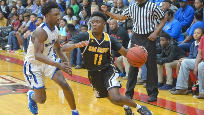 Oak Grove's Winceton Edwards drives toward the basket Friday during the Warriors' game against Meridian.