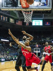 Raptors guard Kyle Lowry (front) watches his shot go behind the basket as Bucks center Greg Monroe defends in the first half Thursday night at the BMO Harris Bradley Center.