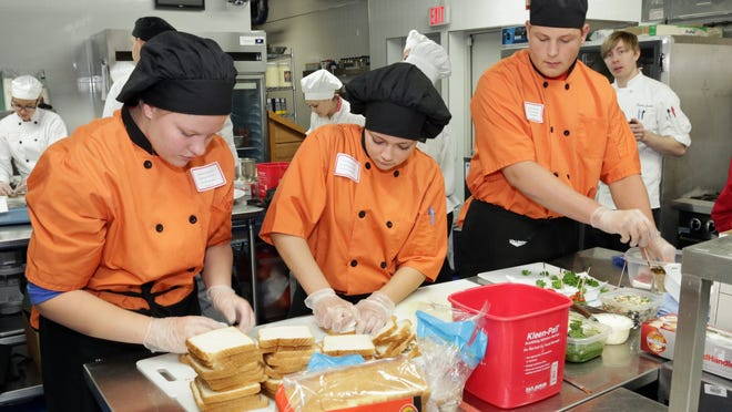 Plymouth students, from left, Hannah McFarlin, Moriah Butters and Derk Schweiger work on creating a sandwich creation at the Lakeshore Culinary Institute in Sheboygan.