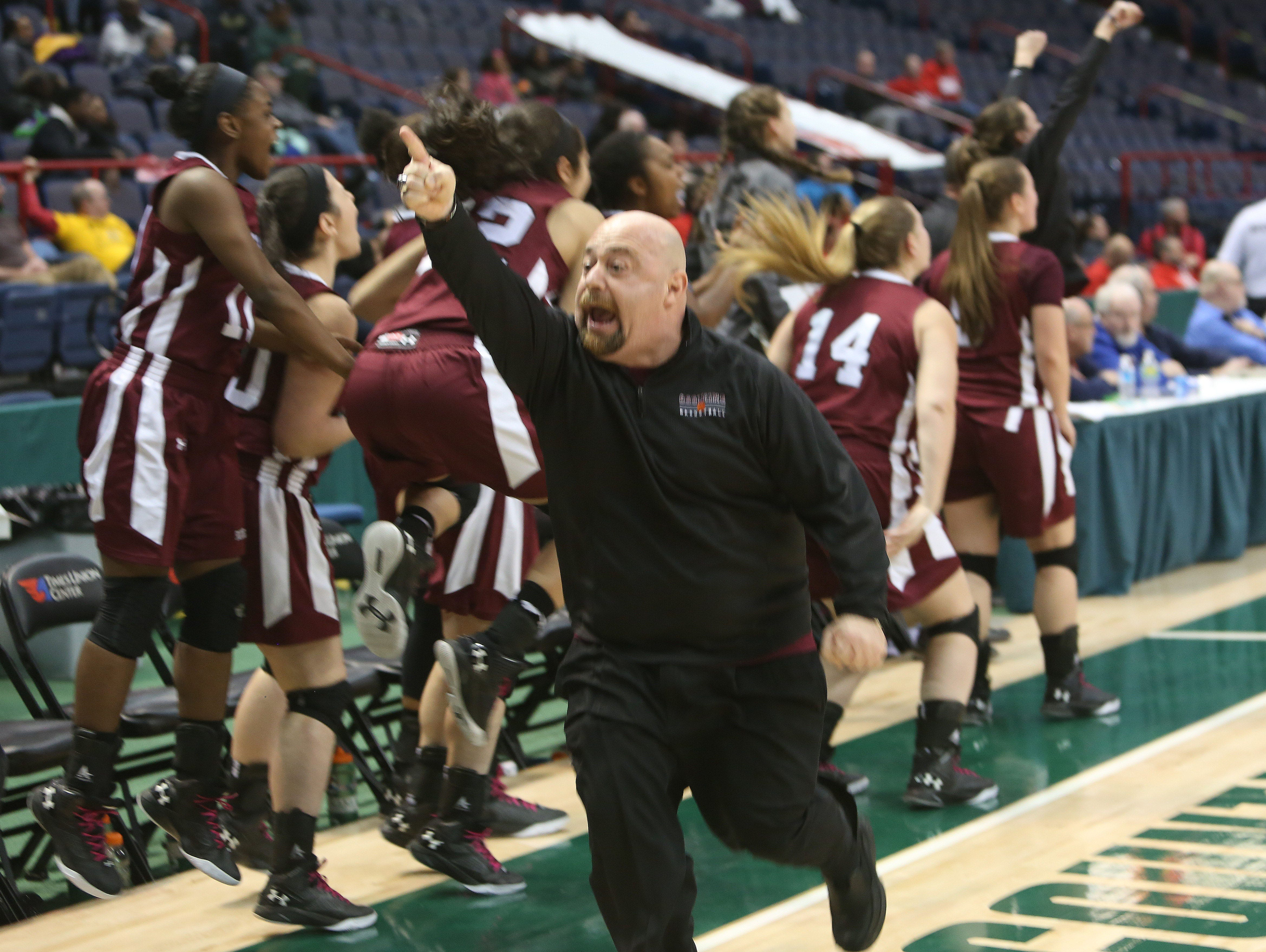 Ossining coach Dan Ricci and his team celebrate a basket late in the game against Long Island Lutheran in the girls Class A final of the New York State Federation Tournament of Champions at the Times Union Center in Albany March 18, 2016.
