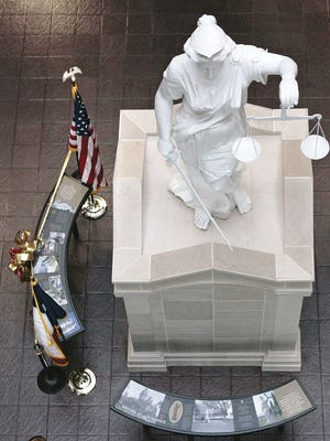 A statue of Lady Justice sits in the lobby of the El Paso County Courthouse.