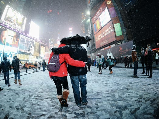 Visitors enjoy the snow on Broadway on Jan. 2 at Times Square in  New York. Up to 7 inches of snow fell across the northeastern USA, causing flight cancellations and closing federal government offices and schools.