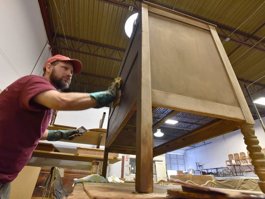 Jim Dillon applies stain to furniture.