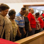 The congregation of Mt. Zion AME Church joins hands and prays for the victims and their families from the shooting in Charleston, North Carolina.