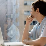Businessman with laptop looking out window