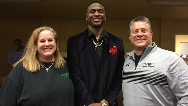 Susan and Rick Bryant flank TCU signee Justin Rogers at the celebration of the Parkway quarterback's signing.