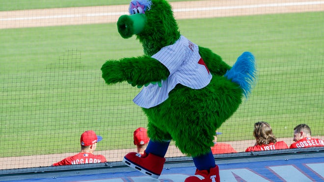FILE - In this Feb. 23, 2020, file photo, the Phillie Phanatic mascot walks on the third-base dugout while the Philadelphia Phillies played the Pittsburgh Pirates in a spring training baseball game in Clearwater, Fla. Mascots are getting a reprieve from Major League Baseball. A month after being tossed out because of health concerns, they're again poised to become inside-the-parkers.