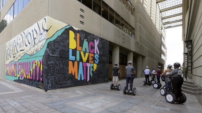 A Segway tour pauses in front of a mural supporting racial equality painted on the side of the Sheraton Hotel Columbus on Capitol Square.