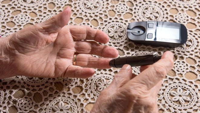 Close up of older woman with glucometer checking blood sugar level at home