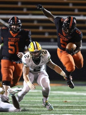 Raekwon Venson of Massillon goes airborne as he tries to elude the tackle of St. Edwards C.J. Hankins in the third quarter.\r