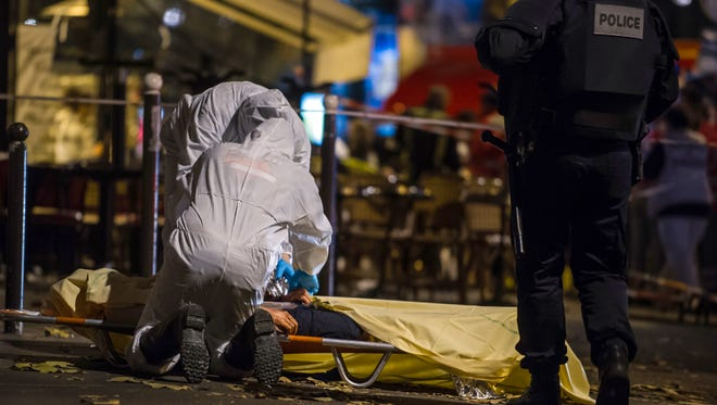 Investigating police officers inspect the lifeless body of a victim of a shooting attack  outside the Bataclan concert hall in Paris, France, Saturday, Nov. 14, 2015. (AP Photo/Kamil Zihnioglu)