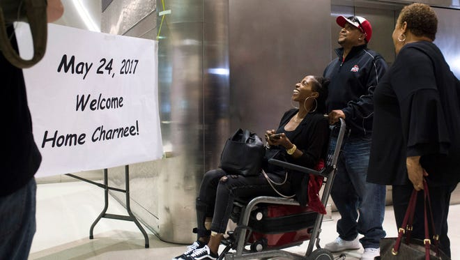 Charnee James, center, laughs at the sign and balloons her family made, as her uncle, Lamar Gullatt, pushes her wheelchair on Wednesday, May 24, 2017 at Detroit Metro Airport in Romulus. The MSU graduate, formerly of Ann Arbor, returned home after being one of seven shot at a pool party April 30, 2017 in in La Jolla, Calif.