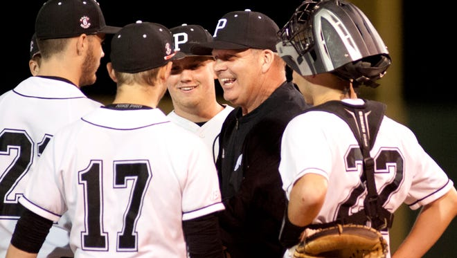 Pleasure Ridge Park head baseball coach Richard Hawks talks to his players at the pitcher's mound during a time-out.April 27, 2018