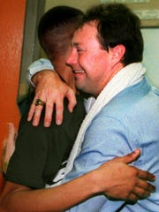 Malone basketball coach Matt Anderson hugs a player after his team won the 1995 Class 1A state title.
