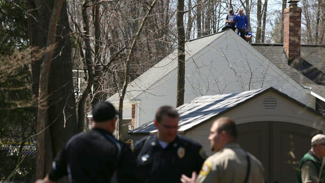 Residents stand on a roof to view a black bear hunkered down in the yard of a home in Midland on Monday, April 30, 2018.