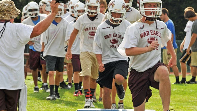 Astronaut High players run drills on the first day of 2015 high school football practice.