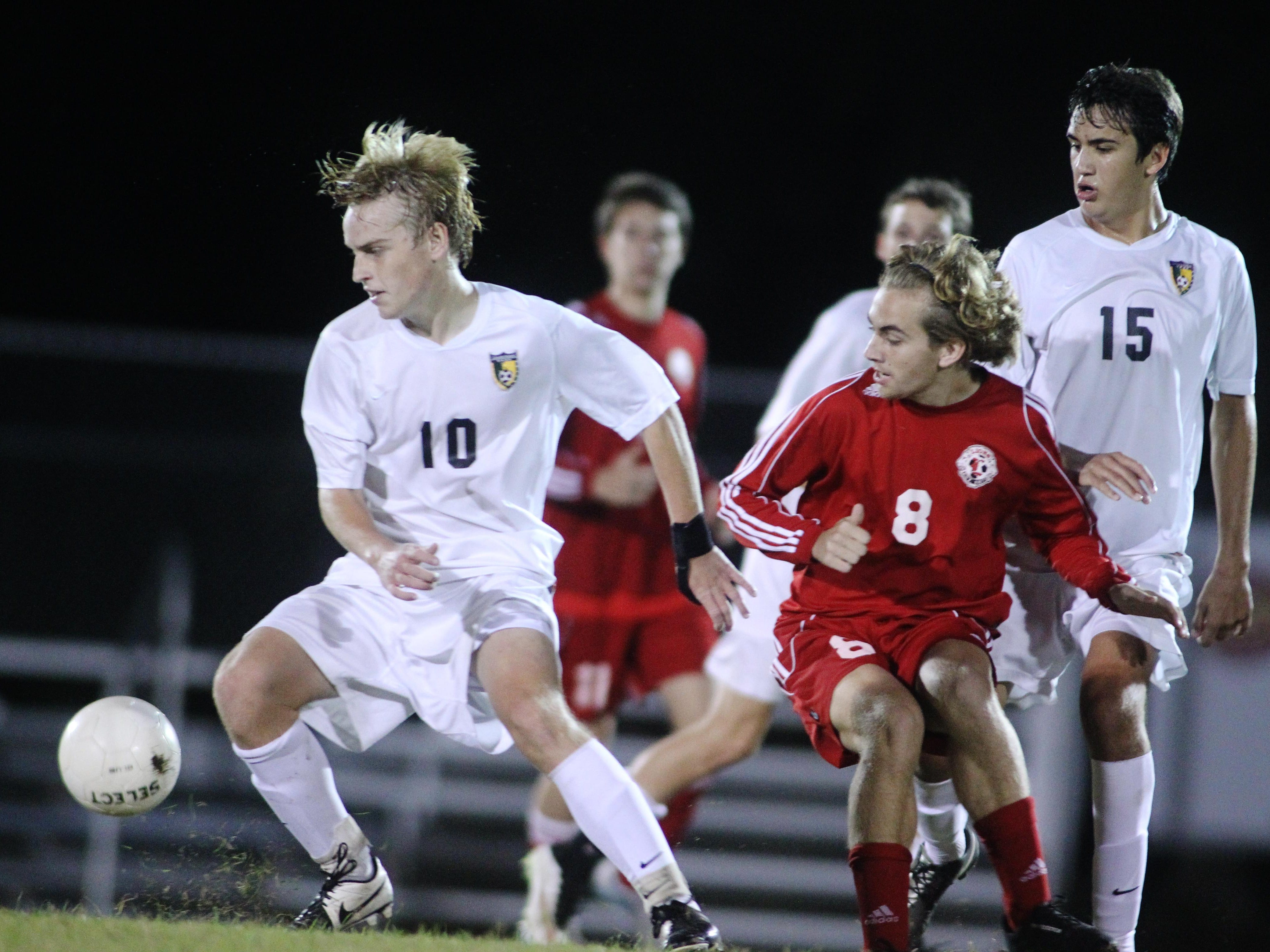 Lincoln's Christian Wnuk and Leon's Jake Kile fight for possession during a game Tuesday night. The Trojans won 2-1.