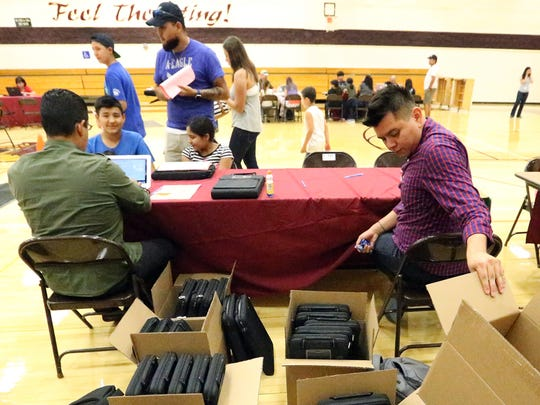 Arturo Briones, right, a computer technician with the El Paso school district unboxes Apple laptop computers from boxes during their distribution to students at Canyon Hills Middle School Friday, August 18. Isaac Chavez and his sister, Arely Chavez, left, were among the more than 600 students to receive a laptop.