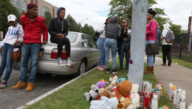 Leaning and sitting on the car, Bicuma Lynn, Isaiah Knox and Phalyn Hayward join other students and friends of Brandon Spears at a memorial set up across from School of the Arts.  Spears, who was fatally shot early Sunday at a downtown hotel, was a former student at the school.