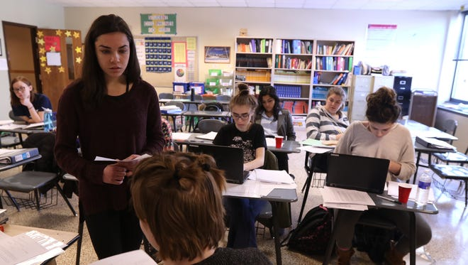 Olivia Segal, acting as a defense attorney, questions Liz Alvut, who is portraying a witness, during Penfield High School's mock trial team practice for an upcoming competition.  Behind them are their teammates Anna Givens and Kayla Ogden seated in the front row.