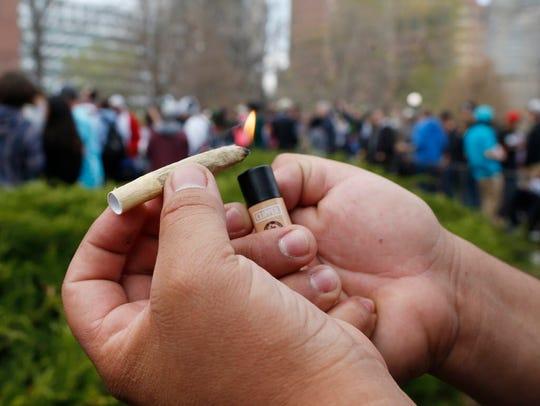 A reveler lights a joint.