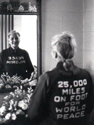 Peace Pilgrim glances in a mirror.