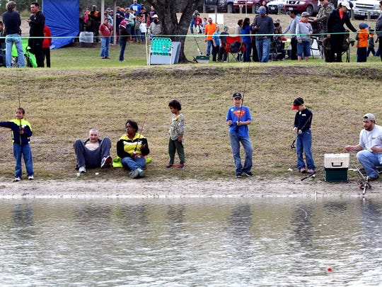 Parents and their children fish for rainbow trout during the 23rd Annual Kid Fish event Saturday Jan. 31, 2015 at Lake Corpus Christi State Park in Mathis.