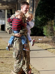 Captain Rob Willoughby holds his twins, Connor and