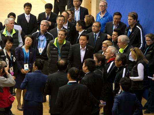 Members of the 2022 Evaluation Commission for the International Olympic Committee (IOC) and representatives of Beijing's 2022 Winter Olympics bid committee listen to a presentation as they tour Capital Indoor Stadium in Beijing, Tuesday, March 24, 2015. (AP Photo/Mark Schiefelbein, Pool)